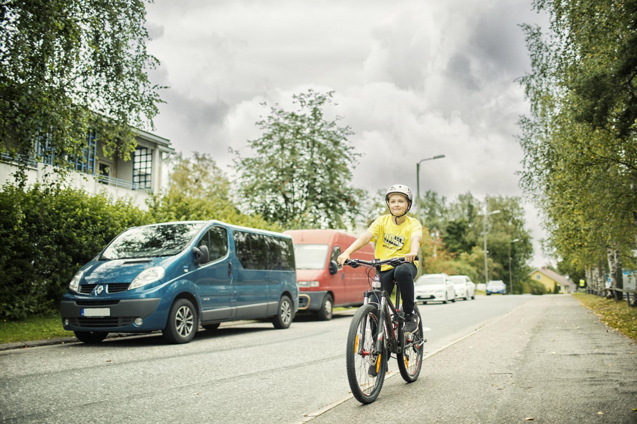 Pyöräilijä pyöräilee pyörätien oikeaa reuana pyöräilykypärä päässä.
