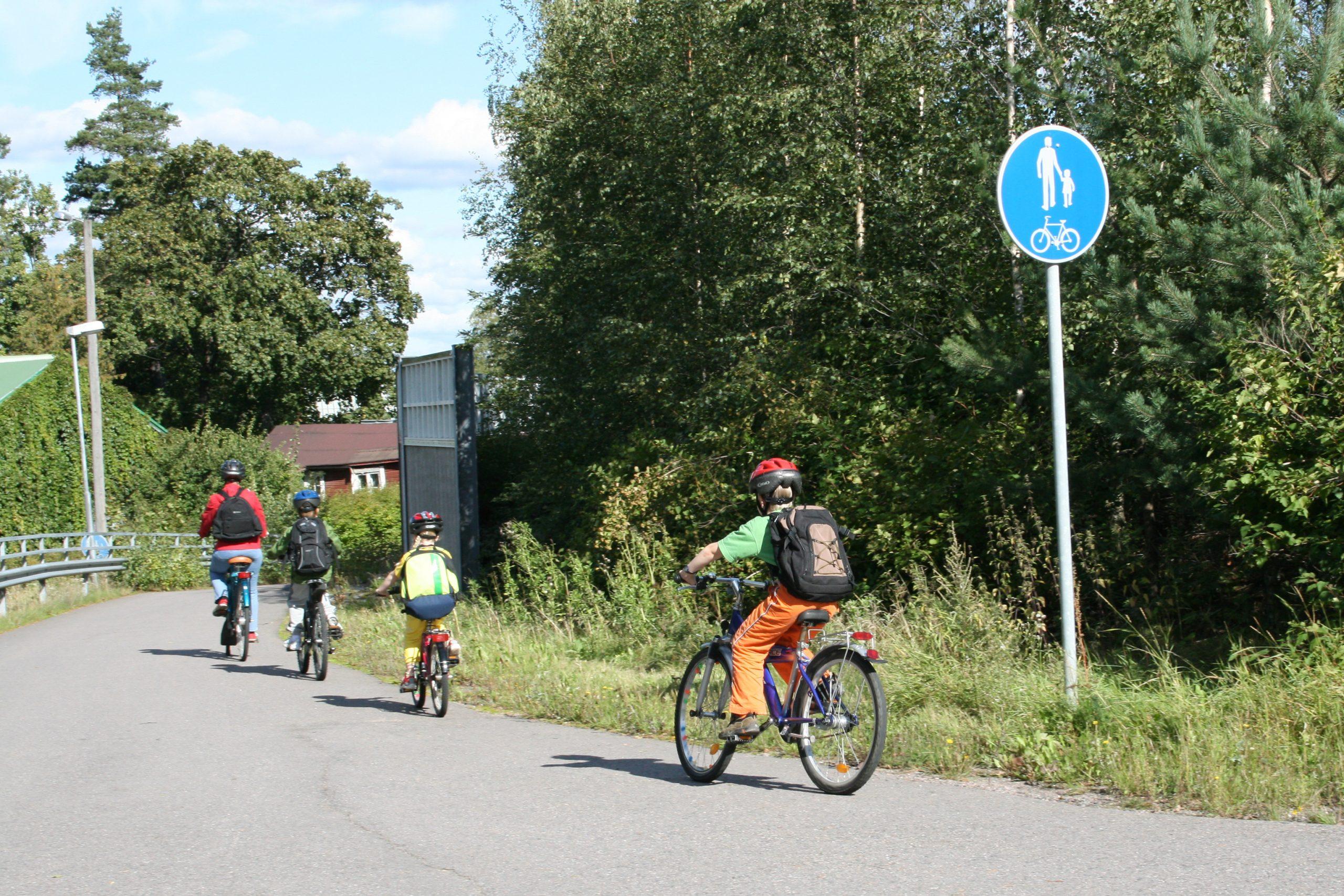 Aikuinen ja lapsia pyörällä liikenteessä