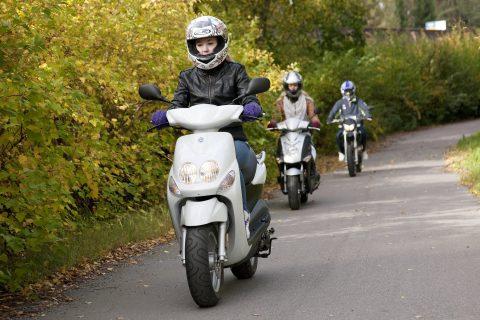 Nuoria mopoilijoita liikenteessä