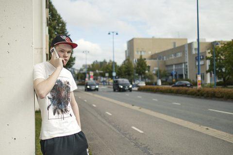 Nuori jalankulkija pysähtyneenä puhumassa puhelimeen