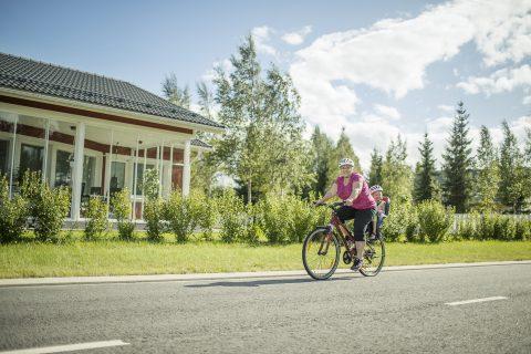 Aikuinen kuljettaa lasta polkupyörällä
