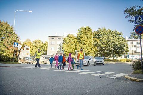 Aikuiset saattamassa kouluikäisiä lapsia tien yli turvallisesti