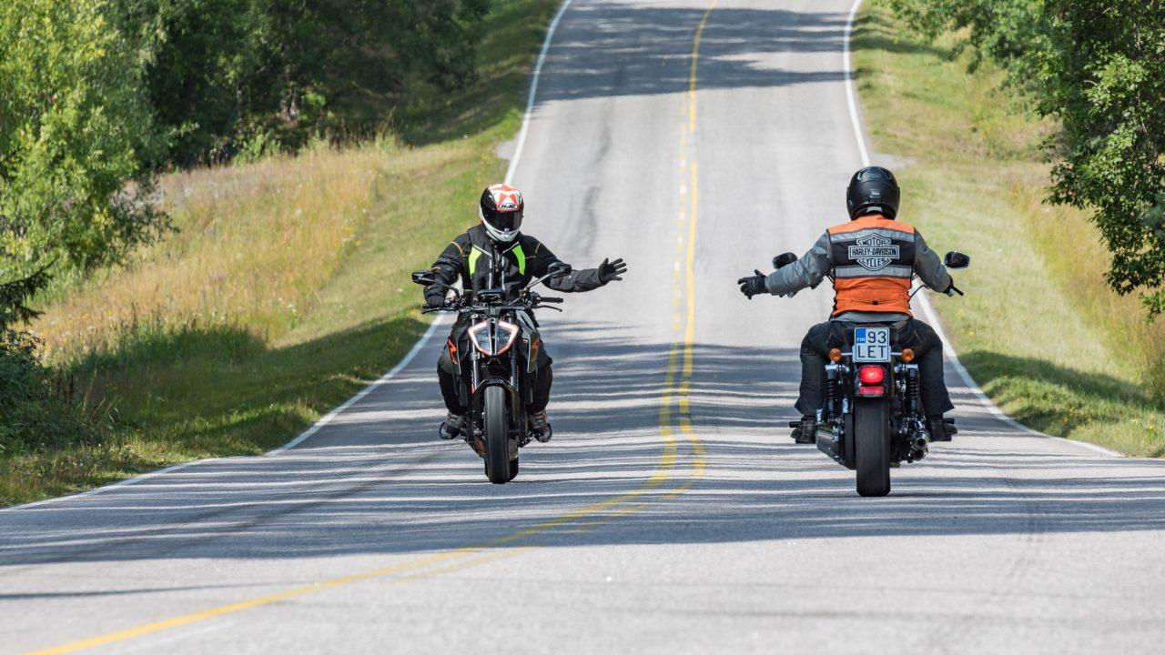 Kaksi motoristia tervehtii toisiaan maantiellä