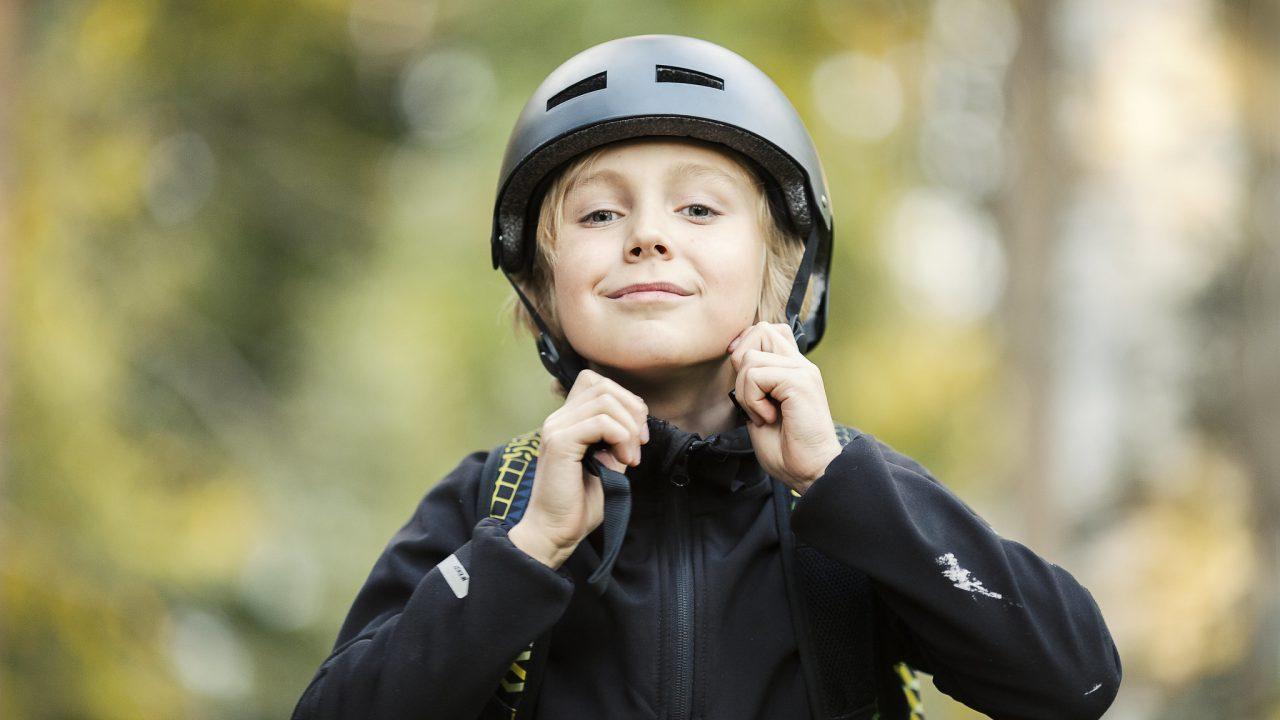 Lapsi laittaa pyöräilykypärää päähän