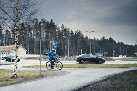 Pyöräilijä kääntyy ja näyttää suuntamerkkiä