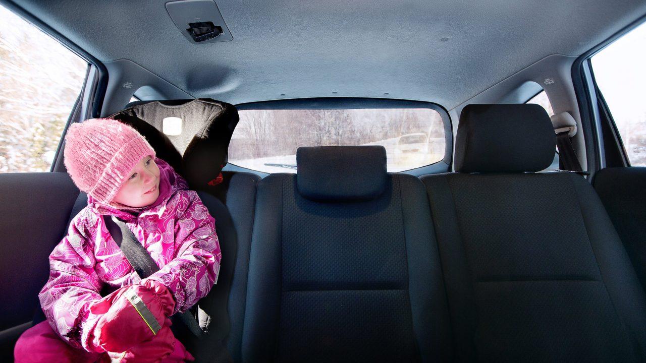 Lapsi istuu autossa turvaistuimessa