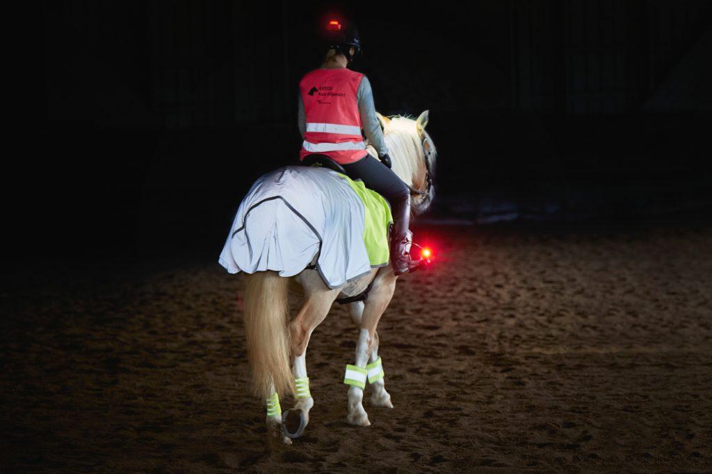 Kuvassa ratsukko, jolla ratsastajalla kypärässä punainen valo osoittamassa taaksepäin sekä myö punainen valo kiinni jalustimessa osoittamassa taaksepäin.
