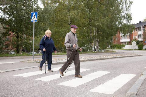 Vanhempi pariskunta ylittää suojatien. Apuna kävelysauvat ja kävelykeppi.