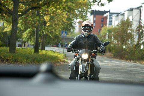 Mopoilija liikenteessä kypärä päässä. Mopoilijalla on yllään hyvät turvavarusteet.
