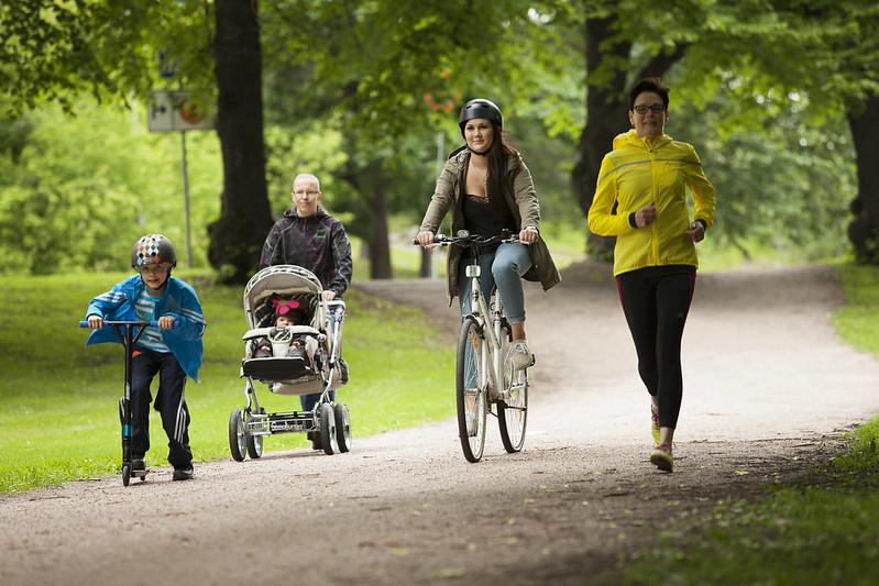 Pyöräilijöitä ja kävelijöitä puistoympäristössä