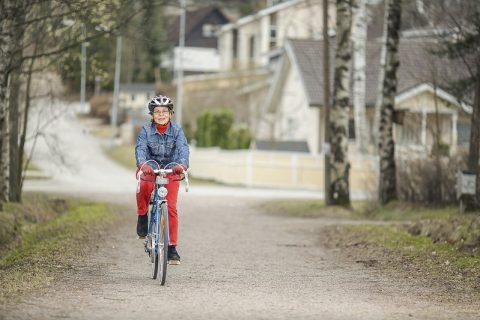 Iäkäs pyöräilijä kypärä päässä pyörätiellä