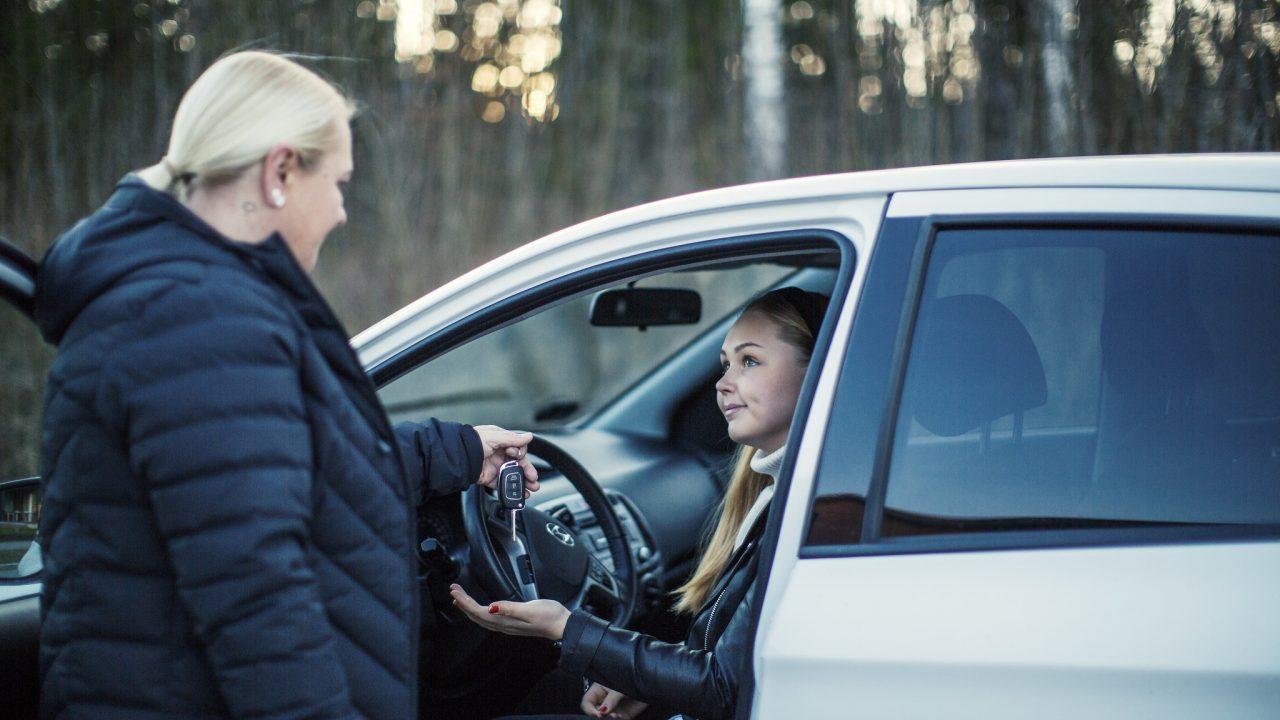 Äiti antaa auton avaimet lapselleen, joka istuu auton etupenkillä. Kuva: Nina Mönkkönen/Liikenneturva