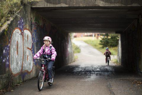 Lapsi pyöräilee alikulkutunnelista ulos.