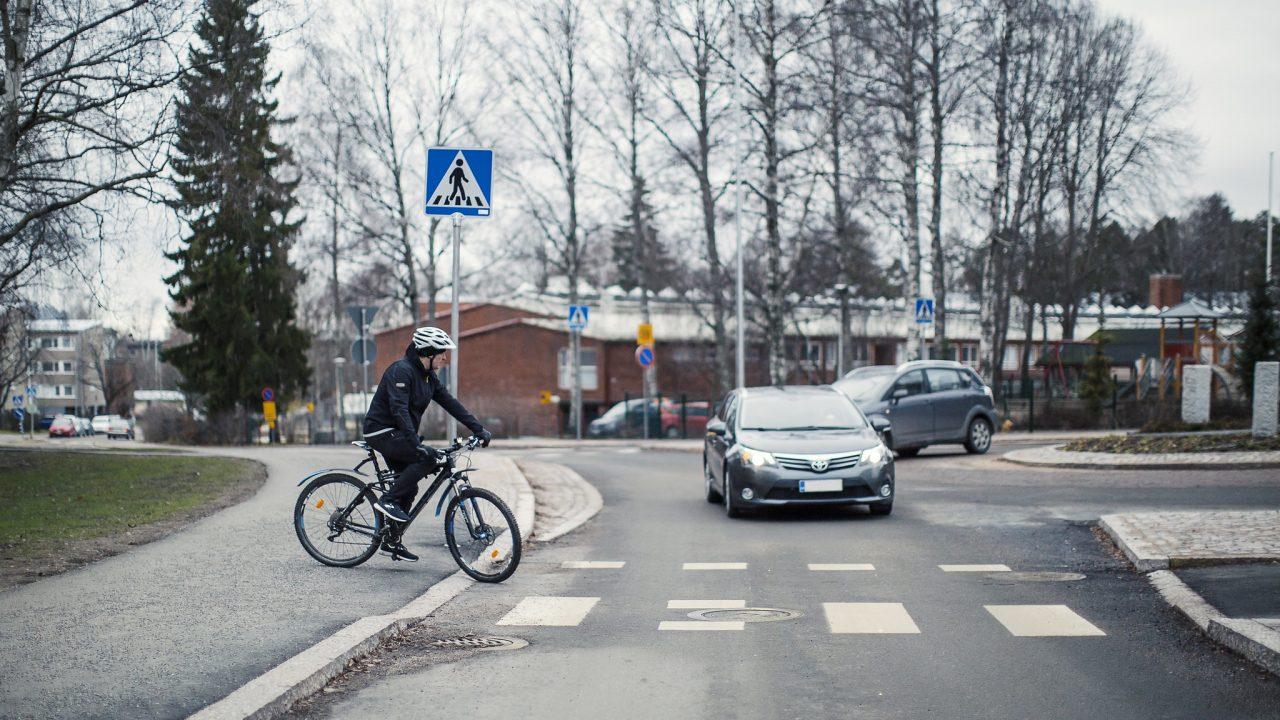 Pyöräilijä ylittää tien, liikenneympyrästä poistuva auto väistää.