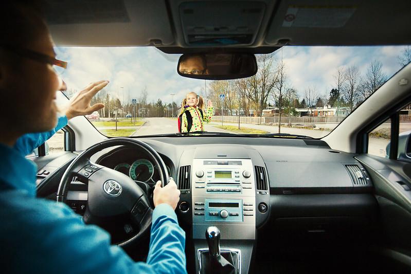 Autoilija tervehtii suojatietä ylittävää lasta.