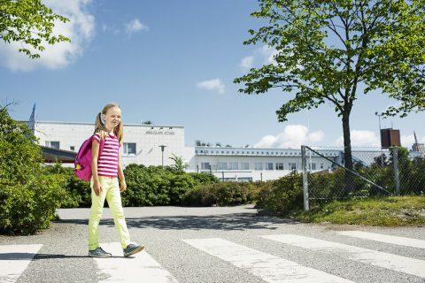 Lapsi ylittää suojatietä koulun edustalla.