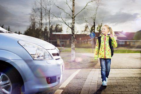 Lapsi ylittää suojatien kuljettajan antaessa tietä.