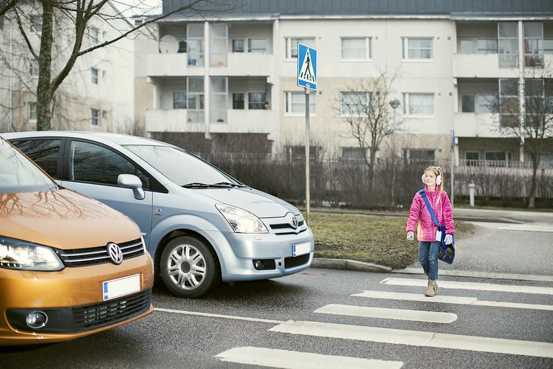 Lapsi ylittämässä suojatietä. Kaksi autoa pysähtynyt suojatien eteen antamaan tilaa lapselle.