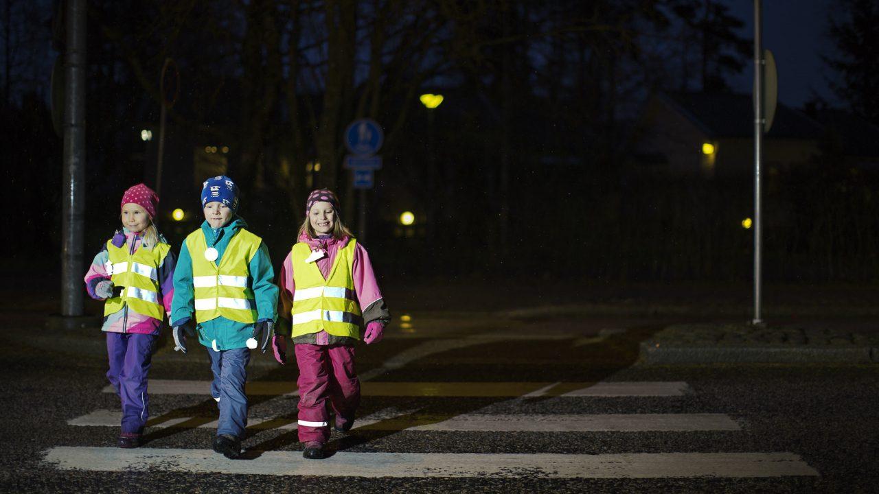 Kolme lasta ylittää suojatietä varusteinaan heijastinliivi ja heijastimia.