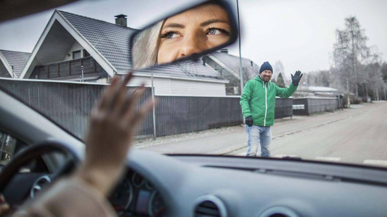 Autoilija antaa jalankulkijalle tietä suojatiellä, ja jalankulkija heilauttaa kättään kiitokseksi.