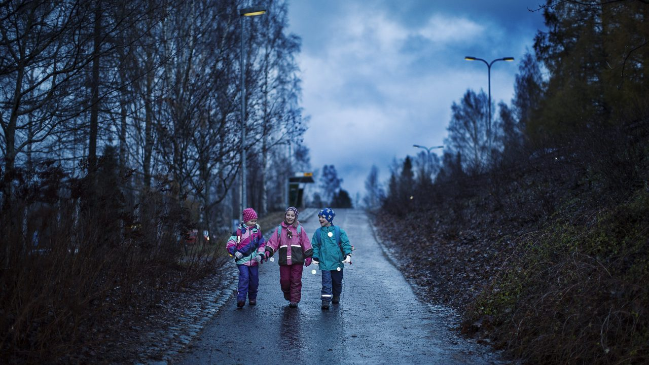 Lapset kävelevät tiellä heijastimet heiluen.