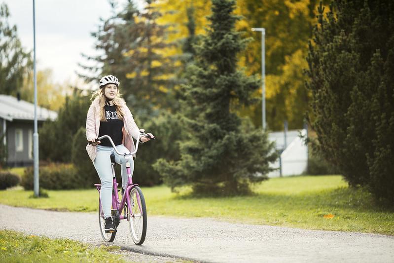 Nuori pyöräilee kypärä päässä