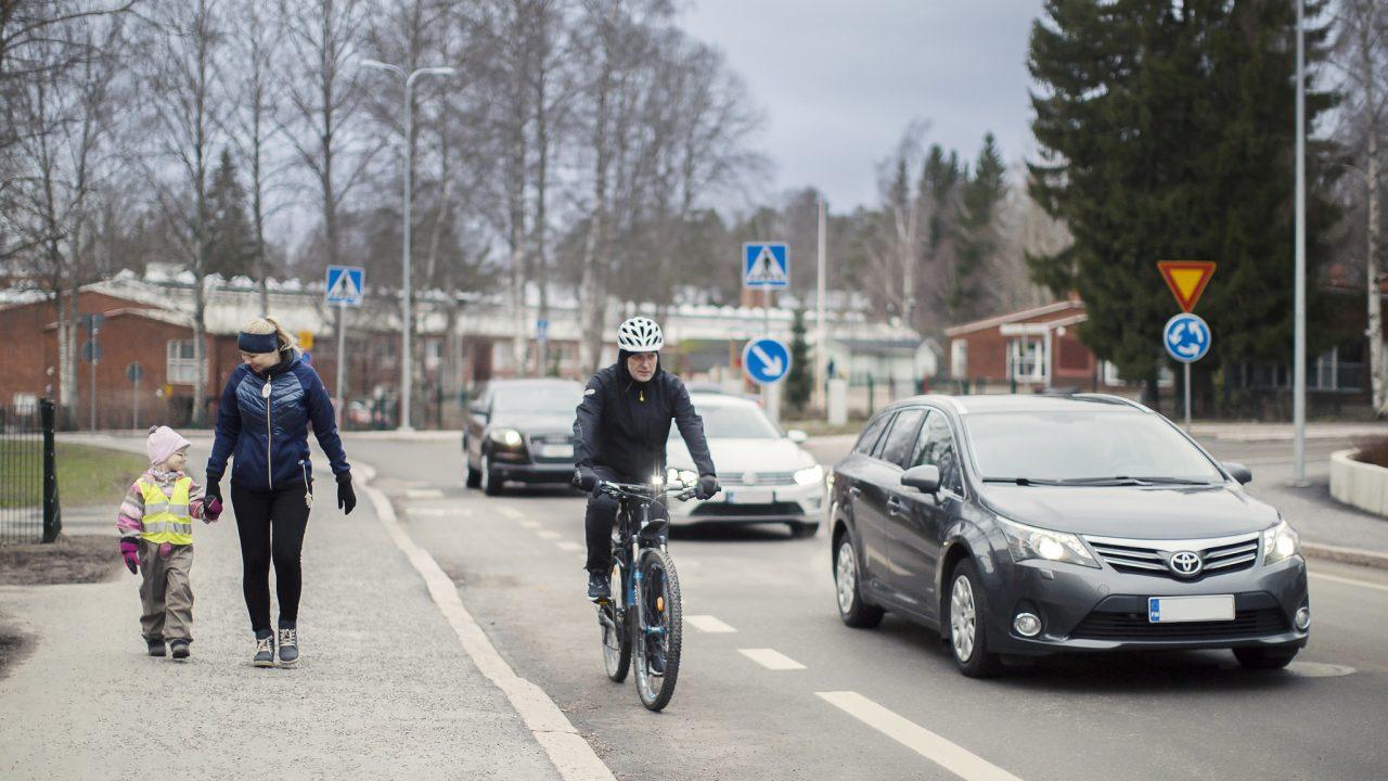 Jalankulkijat jalkakäytävällä, pyöräilijä pyöräkaistalla, auto ajoradalla.