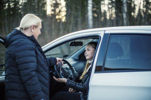 Äiti antaa avaimet tyttärelleen, joka istuu auton etupenkillä.