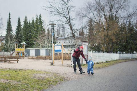 Isä opastaa lastaan liikenteessä.