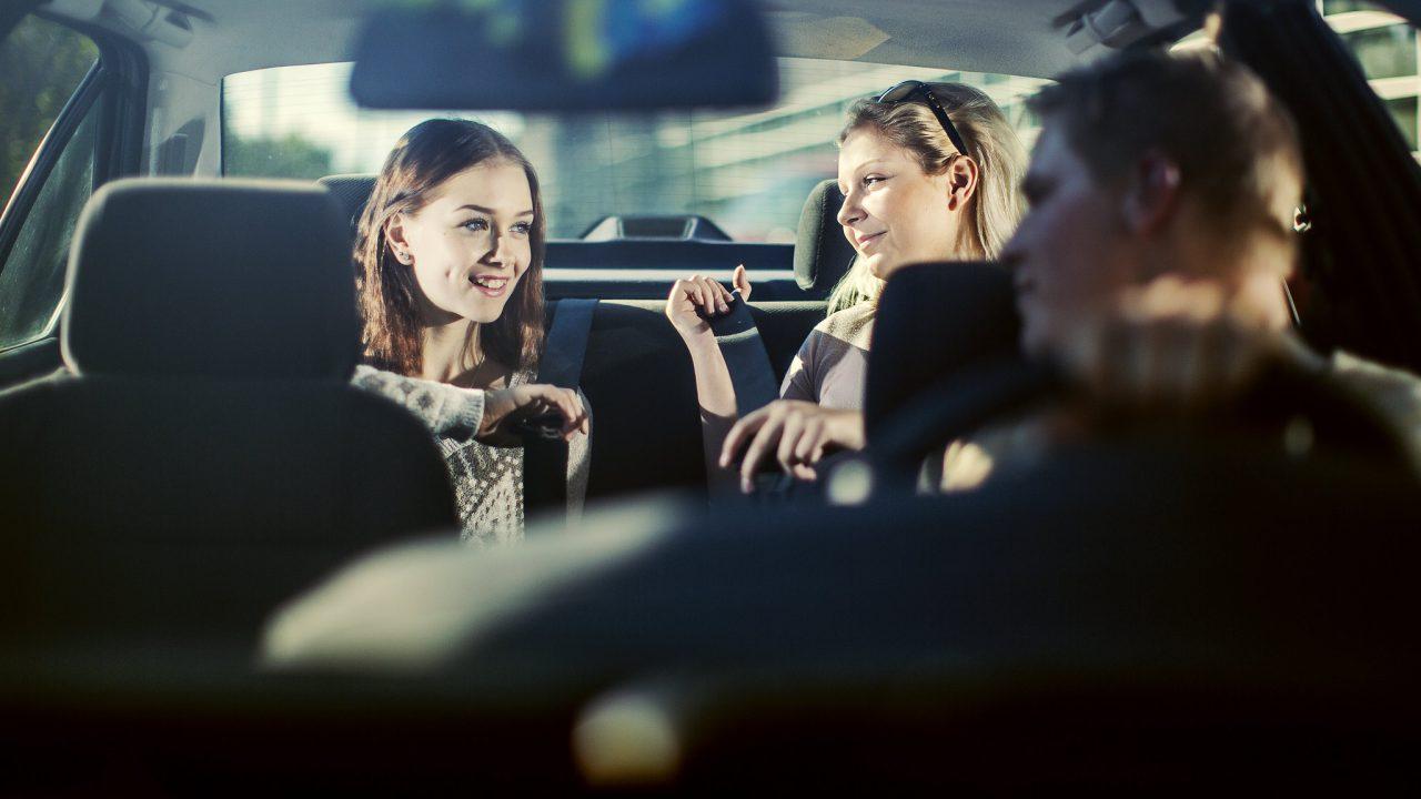 Nuoret kiinnitävät turvavöitä auton takapenkillä