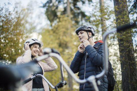 Kaksi nuorta pyöräilijää kiinnittää pyöräilykypäriä