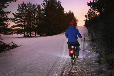 Pyöräilijä pyöräilee hämärässä, tiellä lunta. Punainen takavalo loistaa.