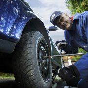 Mies vaihtaa renkaita autoon.