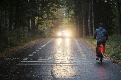 Pyöräilijä pyöräilee maantiellä, punainen takavalo loistaa. Auto on tulossa vastaan.