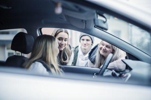 Nuori kuski ratissa, kavereita kurkkii auton ikkunasta sisään.