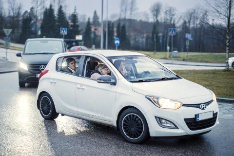 Kaksi autoa peräkkäin, joissa molemmissa palaa ajovalot.